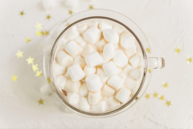 Top view of cup of hot delicious cocoa drink with marshmallows on gold stars