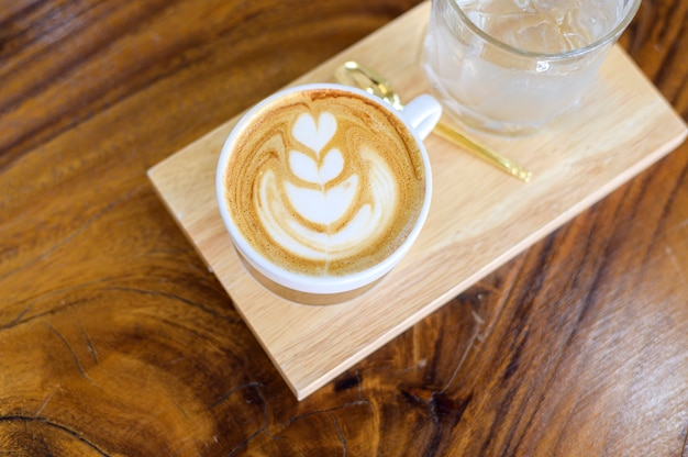 Top view of cup of hot latte art on wooden table background