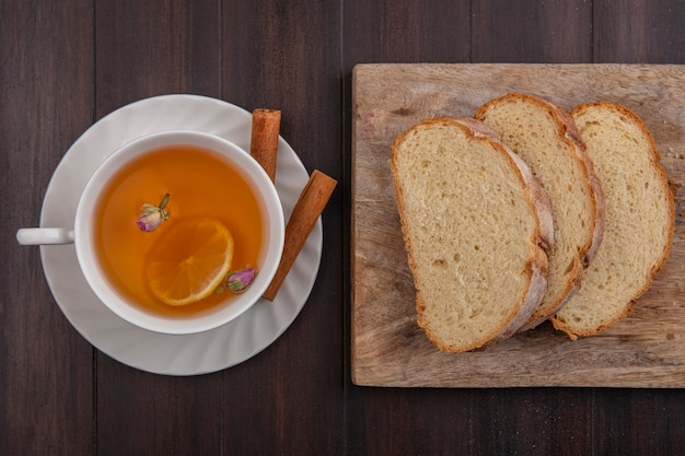 Top view of cup of hot toddy with lemon flower inside and cinnamon on saucer with sliced crusty bread on cutting board on wooden background