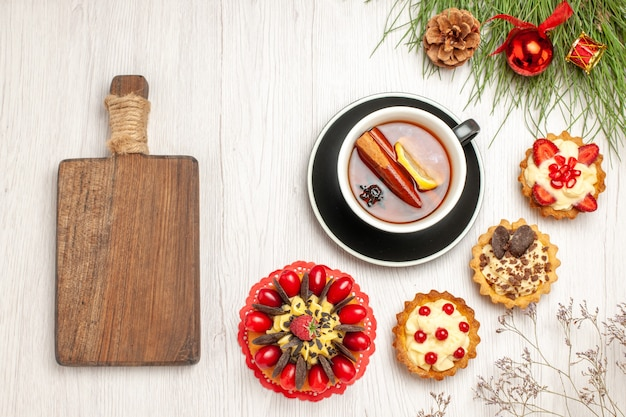 Top view a cup of lemon cinnamon tea berry cake tarts and the pine tree leaves with christmas toys and a chopping board on the white wooden ground