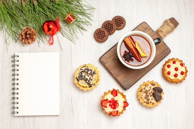 Top view a cup of lemon cinnamon tea on the chopping board tarts cookies and the pine tree leaves with christmas toys and a notebook on the white wooden ground