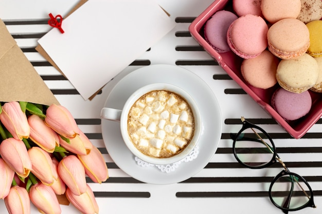 Top view of cup of marshmallows with tulips and macarons