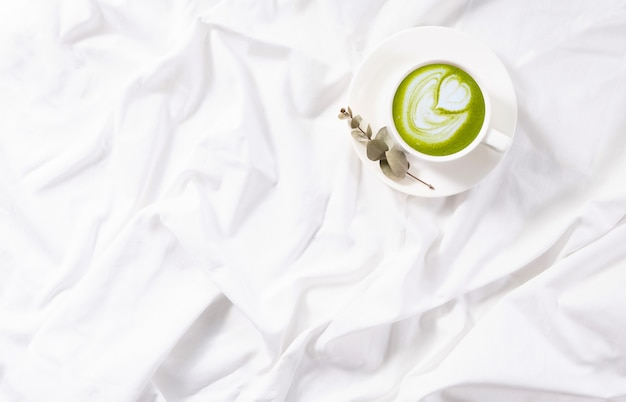 Top view cup of matcha latte in bed. cozy flatlay. morning routine. copy space. concept minimalism