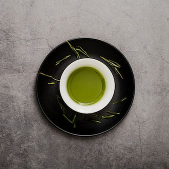 Top view of cup of matcha tea on plate