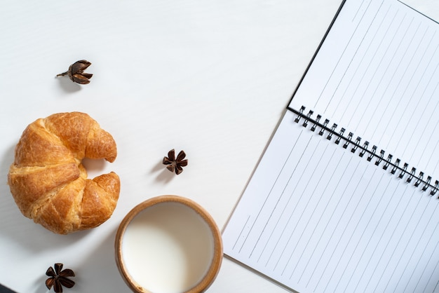 Top view of cup of milk, note book, croissant on wooden table