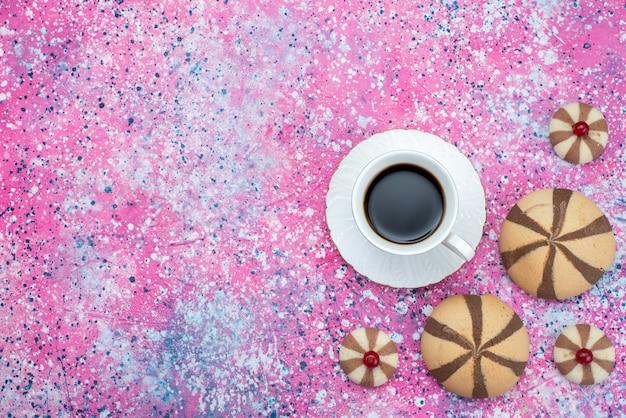 色付きの背景ビスケット砂糖甘い色のチョコレートクッキーと共にコーヒーのトップビューカップ