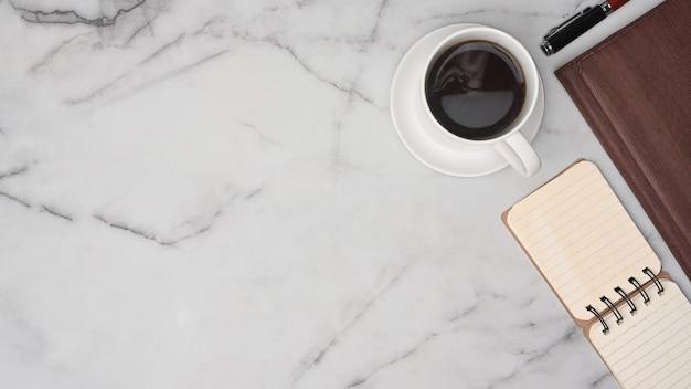 Чашка кофе и ноутбук вид сверху на мраморном фоне.