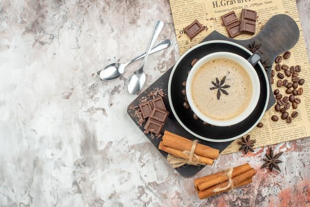 木のサービングボード上のコーヒーチョコレートシナモンスティックのトップビューカップソーサーのローストコーヒー豆はテーブルのない場所にスプーンをアニスします