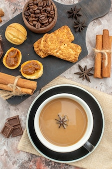 アニスチョコレートシナモンで味付けされたコーヒーのトップビューカップは、テーブルのボウルにある木の板のローストコーヒー豆にクッキーを貼り付けます