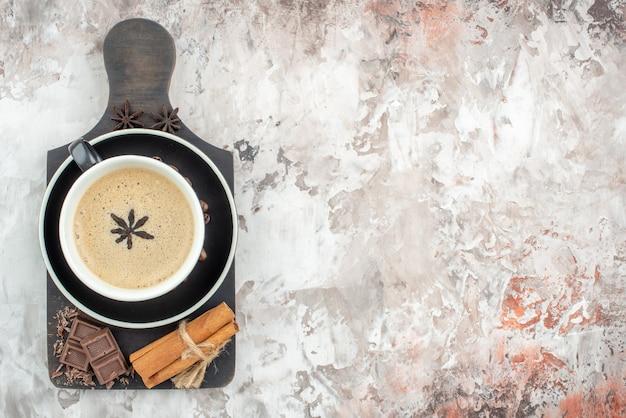 木の板にアニスチョコレートシナモンスティックで味付けされたコーヒーのトップビューカップは、空きスペースのあるテーブルの受け皿にコーヒー豆をローストしました