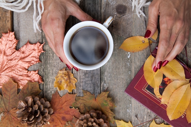 단풍, 콘 나무 테이블 배경에 여성 손에 커피의 상위 뷰 컵