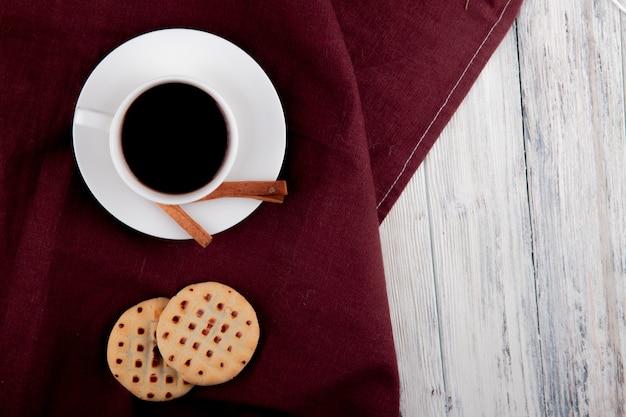 トップビューコーヒーのカップの左側にシナモンクッキーを充填し、白い木製の背景にスペースをコピー
