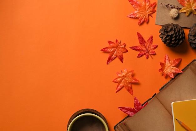 오렌지 배경에 커피, 소나무 콘, 단풍나무 잎이 있는 탑 뷰 컵.