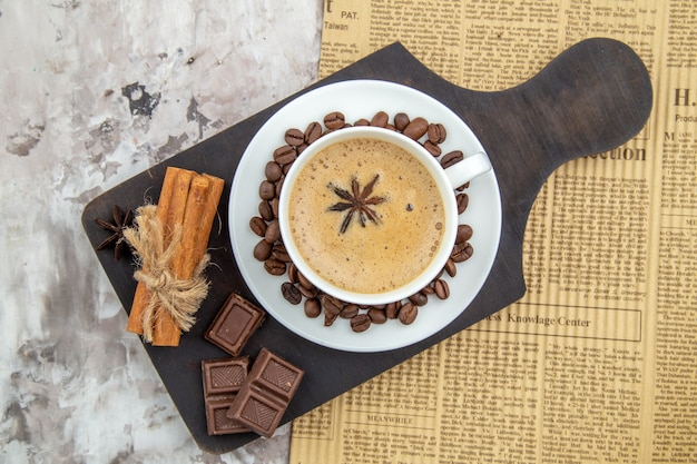 トップビュー一杯のコーヒーとアニスビスケットのローストコーヒー豆の受け皿チョコレートシナモンスティックの木製ボード新聞のテーブル