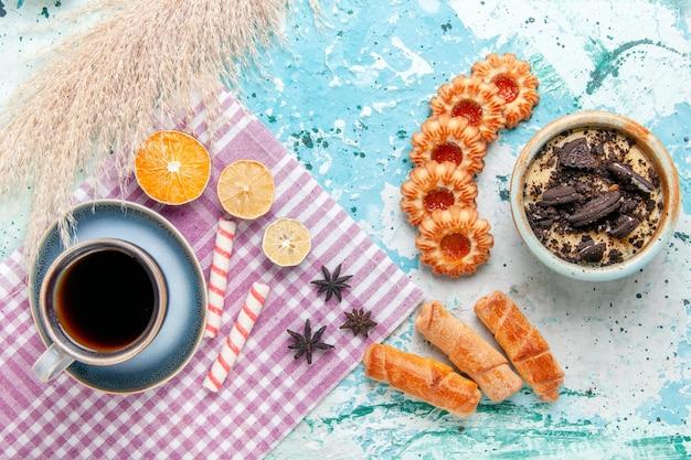 水色のデスクケーキにベーグルとクッキーとコーヒーのトップビューカップは甘い砂糖パイビスケットを焼く