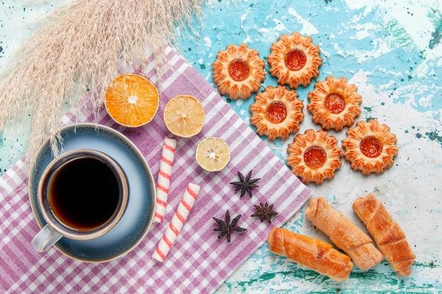 水色の背景のケーキにベーグルとクッキーとコーヒーのトップビューカップは甘い砂糖パイビスケットを焼く
