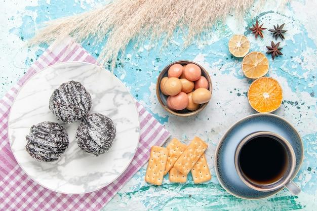 水色の背景のケーキにチョコレートのアイシングケーキとクラッカーとコーヒーのトップビューカップは甘い砂糖パイビスケットを焼く