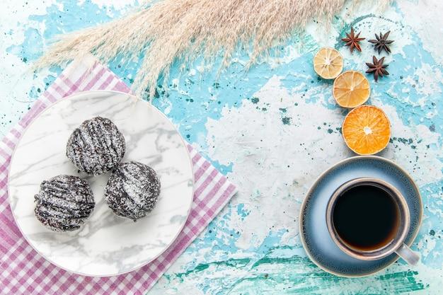 水色の背景のケーキにチョコレートのアイシングケーキとコーヒーのトップビューカップは甘い砂糖パイビスケットを焼く