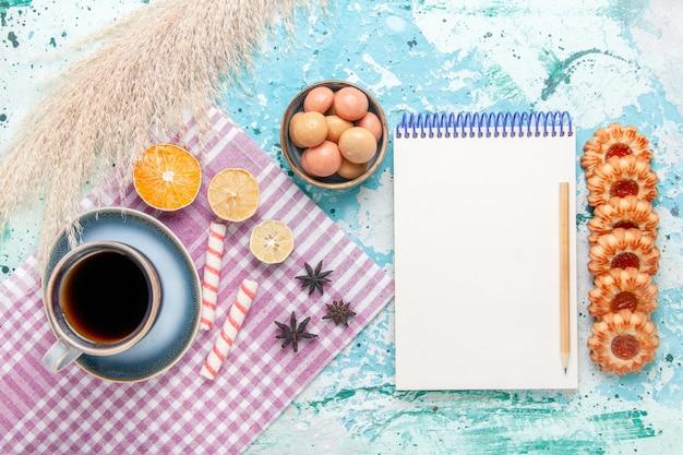 Вид сверху чашка кофе с печеньем и блокнот на голубом фоне, торт, выпечка, сладкий сахарный пирог, печенье