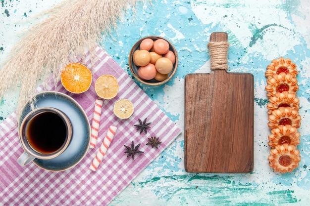 水色の背景のケーキにクッキーとコーヒーのトップビューカップは甘い砂糖パイビスケットを焼く