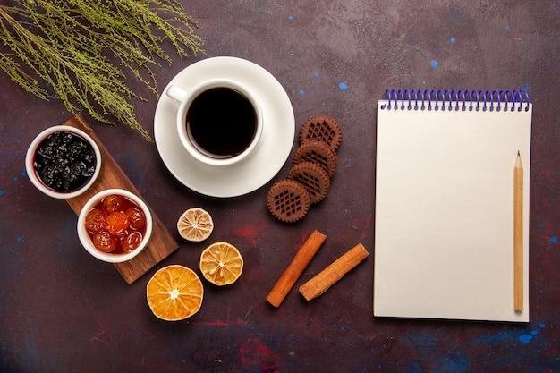 ダークデスクにさまざまなジャムとチョコレートクッキーが入ったトップビューのコーヒーフルーツジャムマーマレードスイート