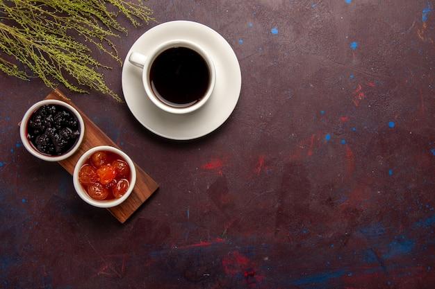 ダークデスクフルーツジャムマーマレードスイートにさまざまなジャムとコーヒーのトップビューカップ