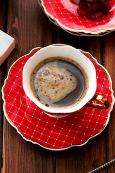 접시에 빨간 컵에 거품을 가진 커피의 상위 뷰 컵