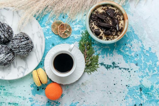 Вид сверху чашка кофе с французскими макаронами и шоколадными пирожными на голубом фоне, выпечка торта, бисквит, сладкий шоколад, сахарный цвет
