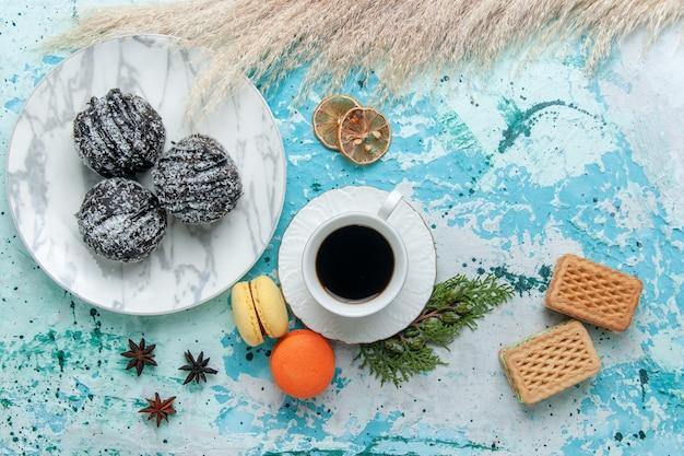 フランスのマカロンワッフルと青い表面のチョコレートケーキとコーヒーのトップビューカップは、ビスケットの甘いチョコレートシュガーカラーを焼きます