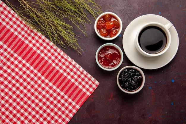 어두운 책상에 과일 잼이있는 커피 한잔의 상위 뷰 달콤한 과일 비스킷 마멀레이드 잼