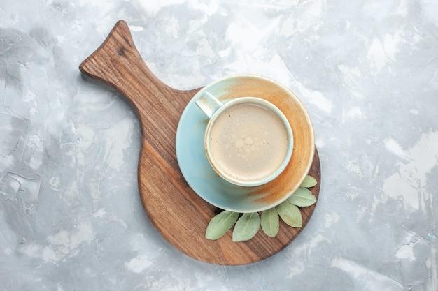 白い机の上のカップの中に牛乳が入ったコーヒーのトップビューカップコーヒーミルクデスクエスプレッソアメリカーノ
