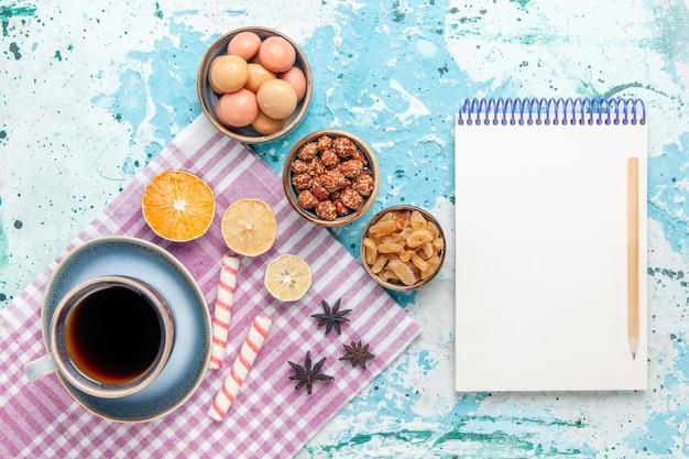 Вид сверху чашка кофе с изюмом и конфитюрами на голубом фоне, выпечка сладкого сахарного бисквита