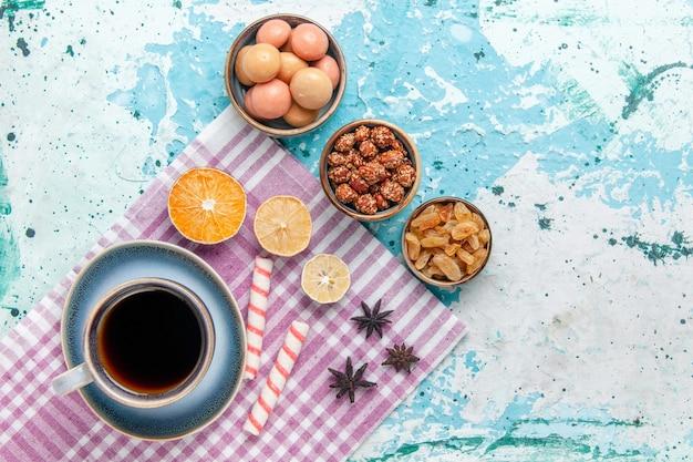水色の背景のケーキにレーズンとコンフィチュールとコーヒーのトップビューカップは甘い砂糖パイビスケットを焼く