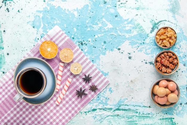 Вид сверху чашка кофе с изюмом и конфитюрами на голубом фоне, выпечка сладкого сахара