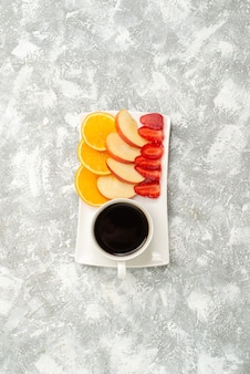 スライスしたリンゴオレンジと白い背景の上のイチゴとコーヒーのトップビューカップ熟した新鮮なまろやかなフルーツ