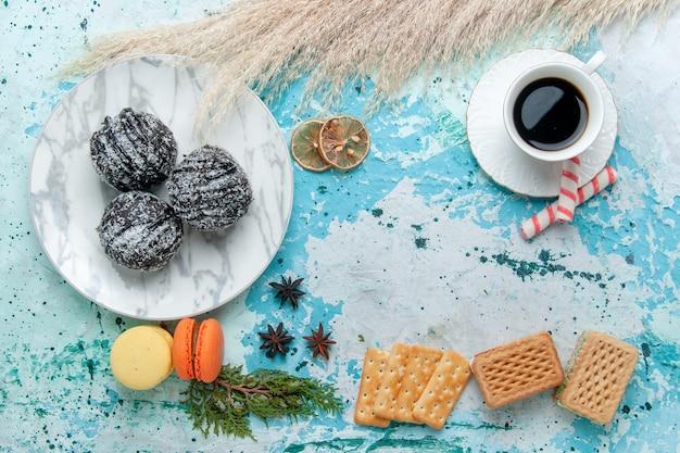 青い背景のケーキにワッフルとチョコレートケーキとコーヒーのトップビューカップはビスケットの甘いチョコレートシュガーカラーを焼きます