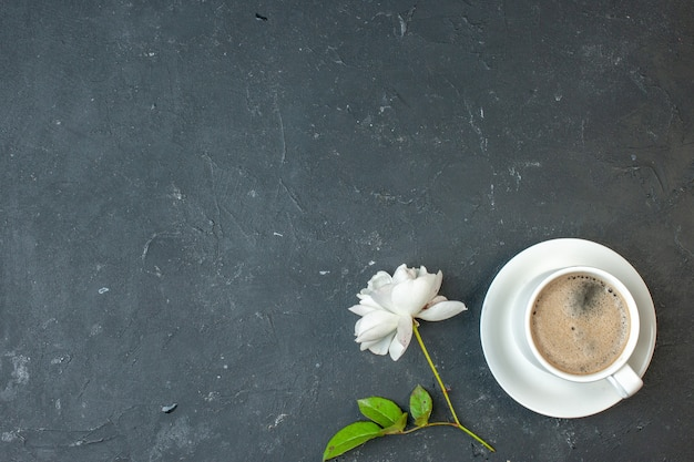 暗いテーブルの上の白い花とコーヒーのトップビューカップ