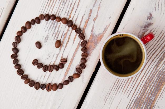 뜨거운 커피와 웃는 얼굴의 상위 뷰 컵. 흰색 나무 표면.