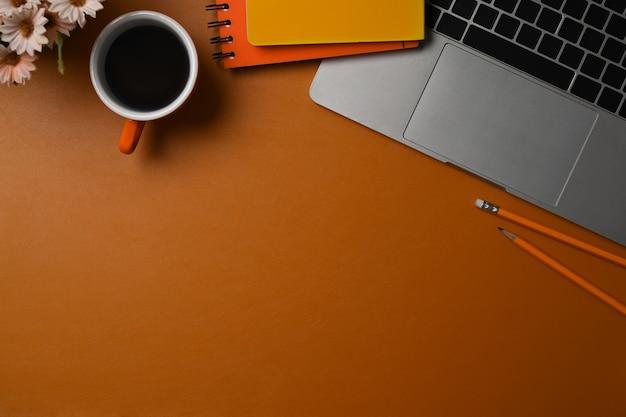 Чашка взгляда сверху портативного компьютера, кофе и тетради на коже бровей.