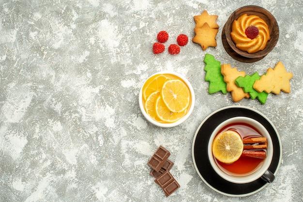 Вид сверху чашка чая, печенье и ломтики лимона в мисках, рождественское печенье на серой поверхности, свободное пространство