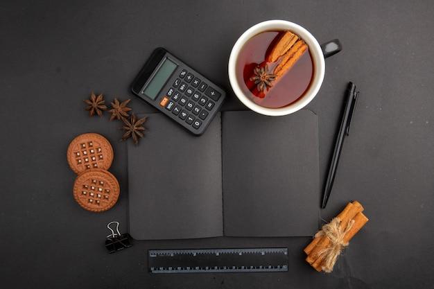 Вид сверху чашка чая, ароматизированная корицей и анисом, калькулятор, блокнот, печенье, ручка, линейка на темном столе