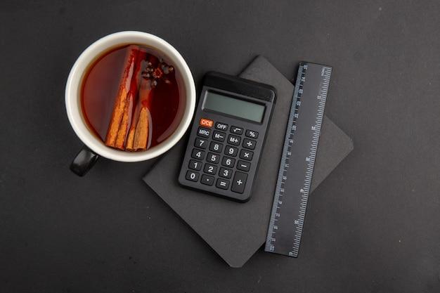 Вид сверху чашка чая, приправленная блокнотом калькулятора линейки корицы на темном столе