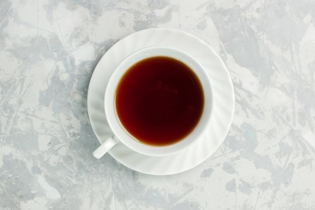 明るい白い机の上にお茶のホットドリンクのトップビューカップ