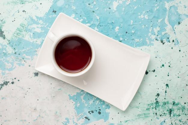 水色の机の上のカップとプレートの中のお茶のトップビューカップ