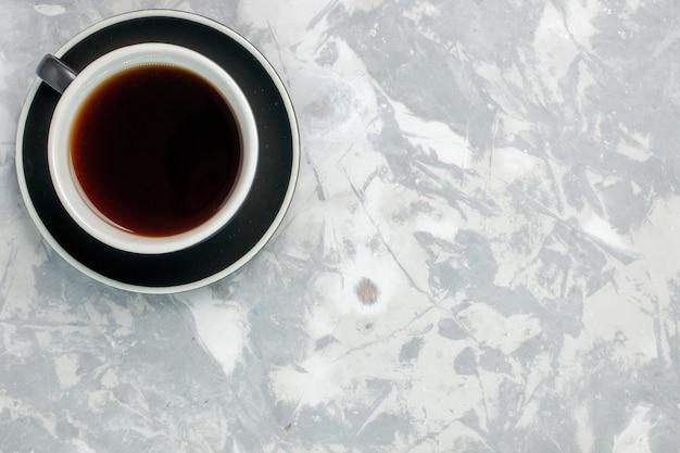 Вид сверху чашка чая внутри чашки и тарелки на светлой белой поверхности