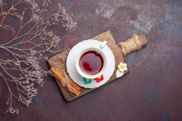 暗い空間にプレートを付けたガラスカップの中にお茶を入れたトップビューカップ