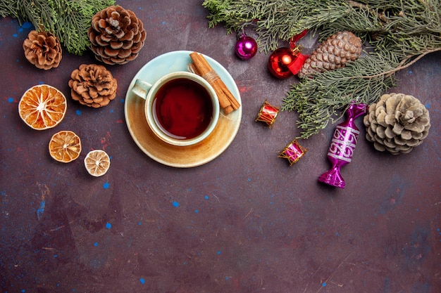 暗い机のお茶を飲むホリデークリスマスのトップビューカップ