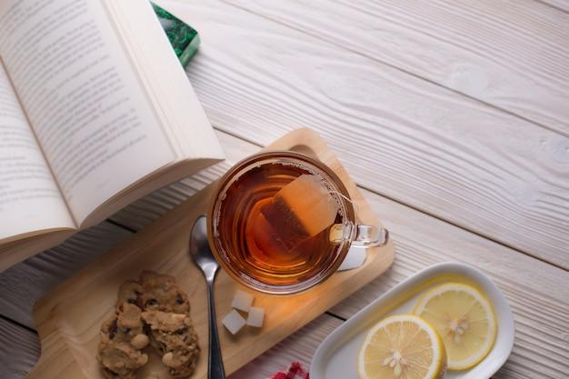 居心地の良い、リラックスした、静かな雰囲気の中で開いた本とクッキーとレモンスライスの木製トレイにお茶のトップビュー