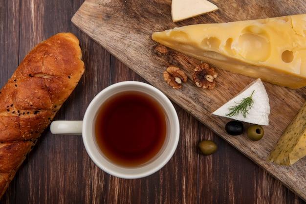 Вид сверху чашка чая с ломтиком сыра маасдам и сыром фета с оливками на доске на деревянном фоне
