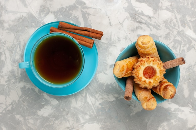 Вид сверху чашка чая с бубликами и корицей на белой поверхности